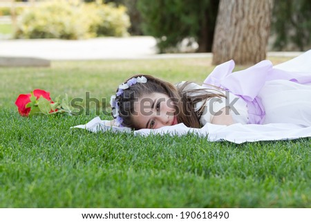 A young girl at a garden celebrating her First Holy Communion - stock photo