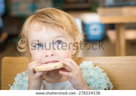 A young girl bites into a cookie at a grocery store. - stock photo