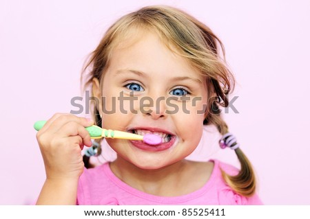 A young girl brushing her teeth - stock photo
