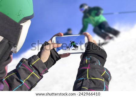 A young girl by mobile phone photographed two skiers - stock photo