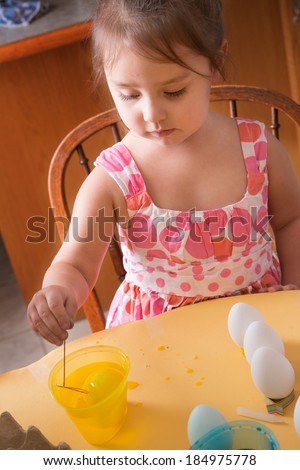 A young girl child is shown coloring Easter egg in yellow dye