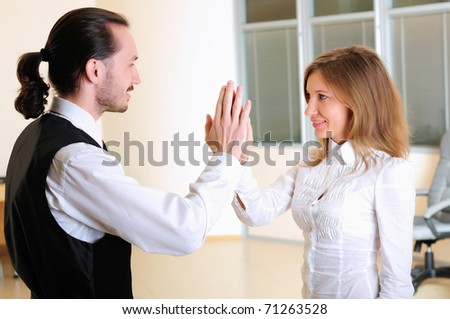 A young girl claps her hands to his colleague in the office.
