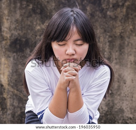 A young girl clasps her hands in prayer.  - stock photo