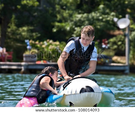A young girl climbing onto a float, helped by a preteen boy, getting ready to be pulled by the boat.