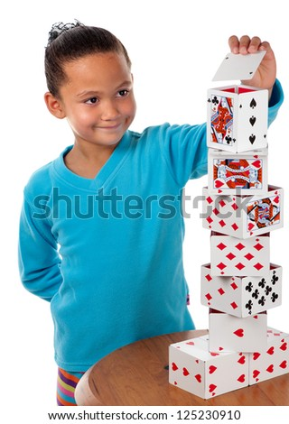 A young girl concentrates whilst laying the final card to complete her playing card tower. - stock photo