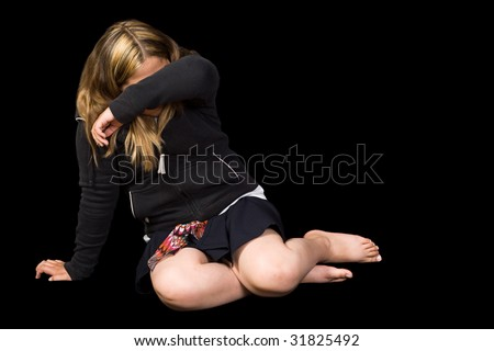 A young girl cowering on the floor trying to protect herself from some abuse, isolated against a black background - stock photo