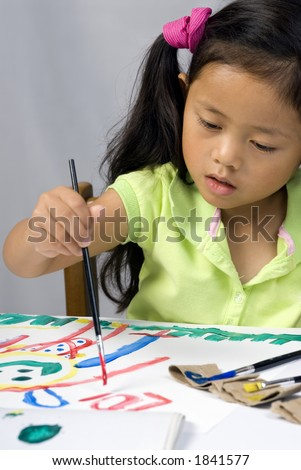 A young girl creates a self portrait with paint. - stock photo
