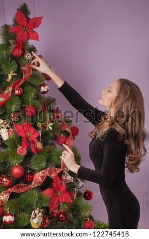 A young girl decorates the Christmas tree - stock photo