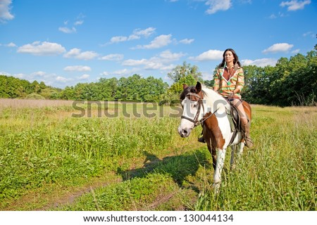 A young girl dressed as an Indian rides a paint horse