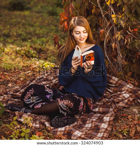 A young girl dressed in a blue sweater, skirt and boots is reading a book sitting on a rug under a tree in autumn park