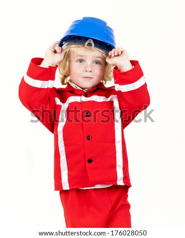 A young girl dressed up in a red suit with a blue hat on. - stock photo
