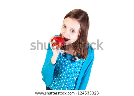 a young girl eating a delicious red apple
