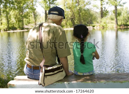 A young girl fishing with her grandpa on a warm summer day.