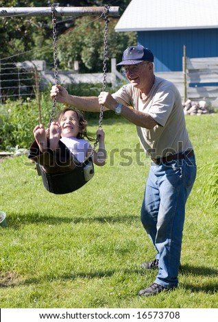 A young girl gets a push on a swing by her grandpa on a warm summer day. - stock photo