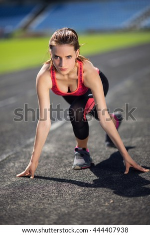 A young girl goes in for sports with mat makes stretching, warm up exercises at the stadium on grass - stock photo