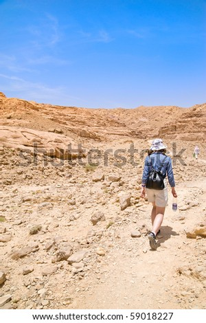 a young girl goes through the desert with a bottle of water - stock photo
