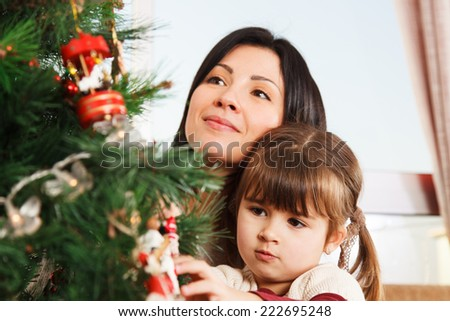 A young girl helps her mother to decorate the family Christmas tree. - stock photo