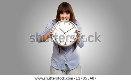 A Young Girl Holding A Clock And Angry On Grey Background