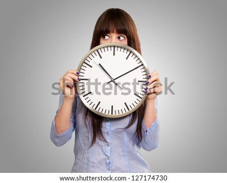 A Young Girl Holding A Clock On Gray Background - stock photo