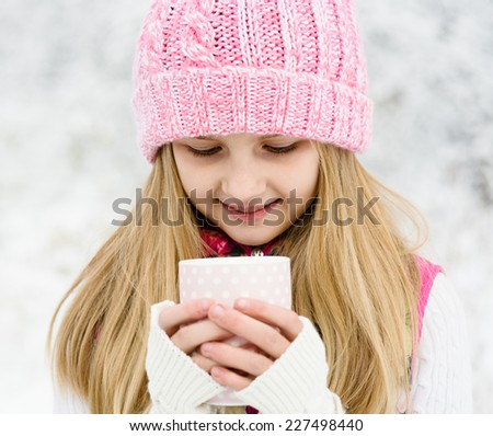 A young girl holding a cup of hot drink and smiling at the background of a winter forest - stock photo