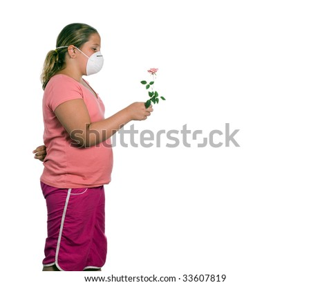 A young girl holding a flower while she wears a mask, isolated against a white background - stock photo