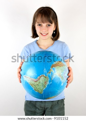 A young girl holding a globe against a white background