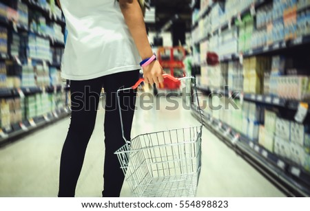 A young girl holding a shopping basket is blurring the image