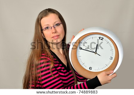 A young girl holding a wall clock against a gray background