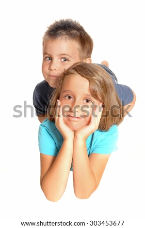 A young girl, holding her face in her hands and her brother is lying on