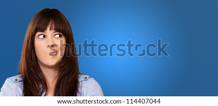 A Young Girl Holding Making Face On Blue Background - stock photo