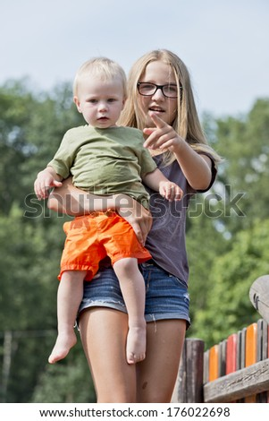 A young girl holds a baby boy and points somewhere. - stock photo