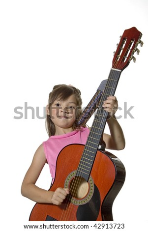 A young girl holds a guitar in this studio photograph
