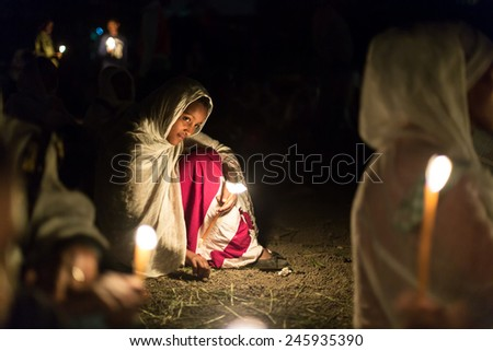 A young girl holds a wax candle during the prayer ceremony of Timket, the Ethiopian Orthodox celebration of Epiphany, on January 19, 2015 in Addis Ababa. - stock photo