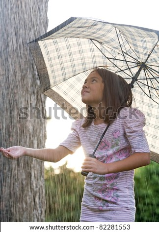A young girl holds an umbrella during a brief rain shower. - stock photo