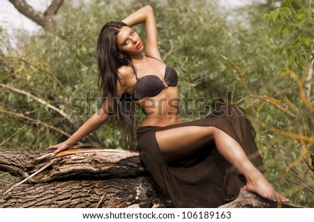 A young girl in a beautiful bathing suit lying on a fallen tree, portrait series of girls in nature