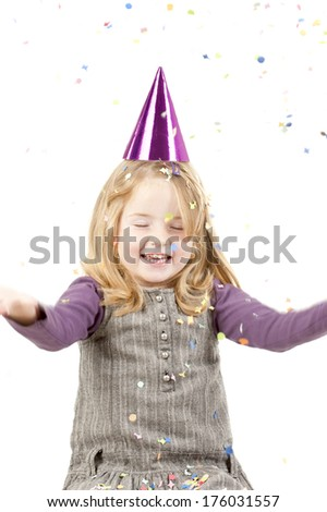 A young girl in a party hat with her arms extended.