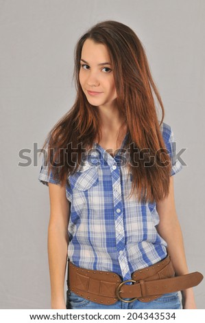 A young girl in a shirt with short sleeves and jeans with a smile looks ahead