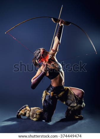 A young girl in image Northern warrior woman shoots an arrow with a knee