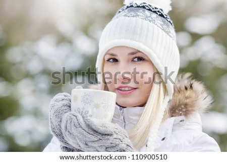A young girl in warm winter clothes holding a cup with a drink on the background of the winter forest, horizontal frame, close up portrait