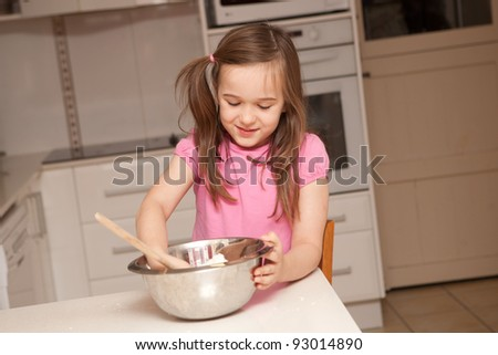 A young girl is baking cupcakes in their kitchen at home - stock photo