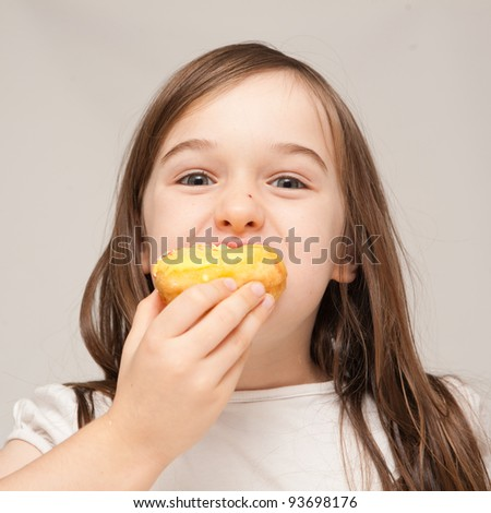 A young girl is eating a donut.  He is enjoying eating unhealthy food.   - stock photo