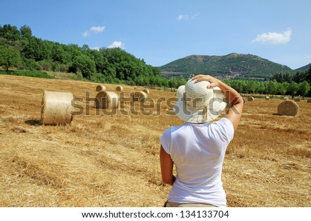 A young girl is looking at a field in Tuscany