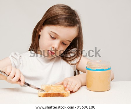 A young girl is making a sandwich consisting of wholemeal bread and peanut butter.