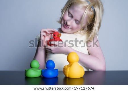 A young girl is playing with colorful rubber ducks.