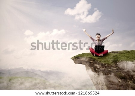 A young girl is sitting on a high mountain with her laptop and arms raised - stock photo