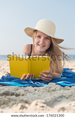 A young girl laying at the beach reading a book.