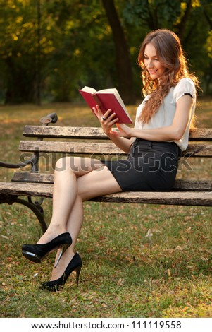 A young girl learns in the park - stock photo