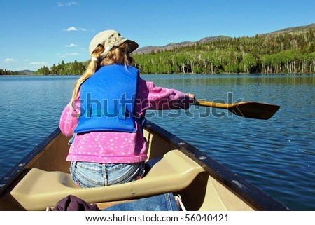 A young girl learns to paddle a canoe on a mountain lake. - stock photo
