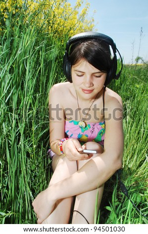 A young girl listening music in a spring field - stock photo