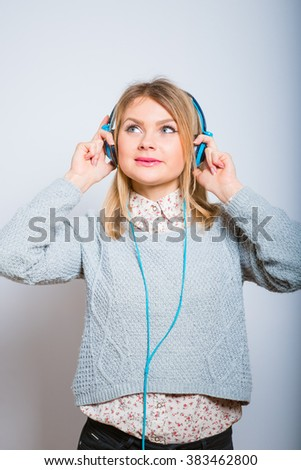 a young girl listening to music on headphones, isolated on a gray background - stock photo